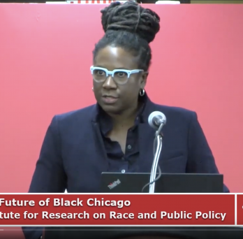 a black woman with blue glasses and her hair pulled up stands at a podium speaking