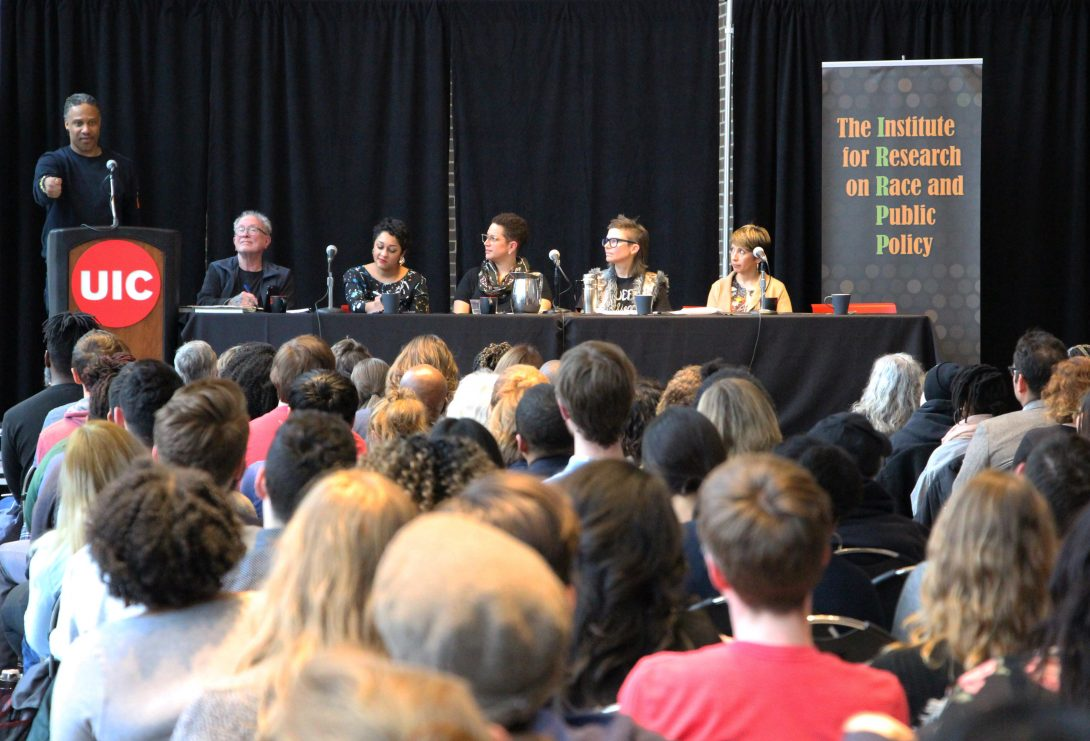 group of people on a panel in front of a room of onlookers