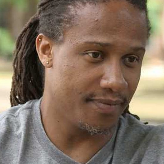 a man in a grey t-shirt looks to one side