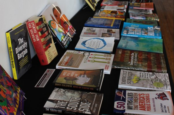 two rows of books related to education laying flat on a black table