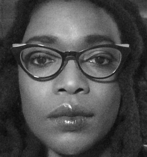 a woman with glasses faces the camera