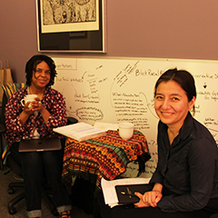 A faculty member and writing coach talking one on one in an office