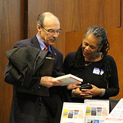 Dean of the College of Urban Planning and Public Affairs looking at a book with former IRRPP Director Beth Richie