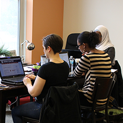 a group of graduate students sit around a table, focusing on typing on their laptops