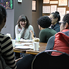 a group of graduate students sit around a table, chatting and smiling